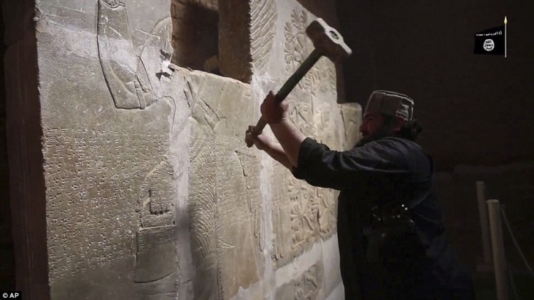 An ISIS militant uses a sledgehammer to destroy a several thousand years old stone slab in a video allegedly showing the group's attack on the ancient ruins of the city of Nimrud, near Mosul, Iraq